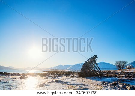 Shipwrecked wooden viking boat on frozen beach in Northern Norway