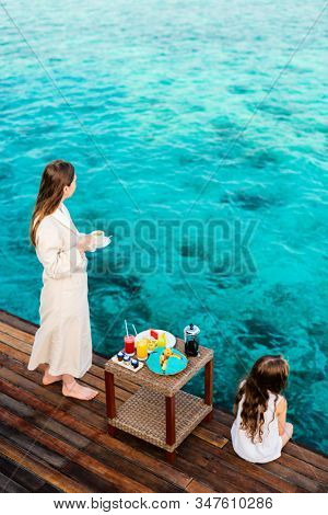 Mother and daughter at wooden dock enjoying ocean view while having breakfast at overwater villa
