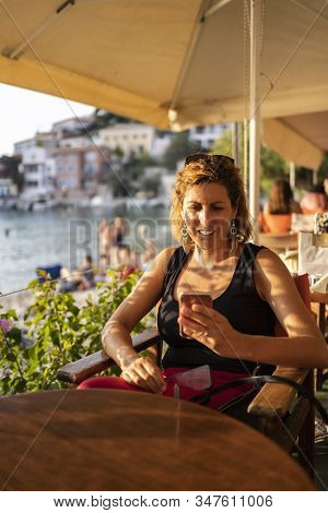 Middle Aged Woman Usin A Smart Phone On A Rerstaurant Near The Sea