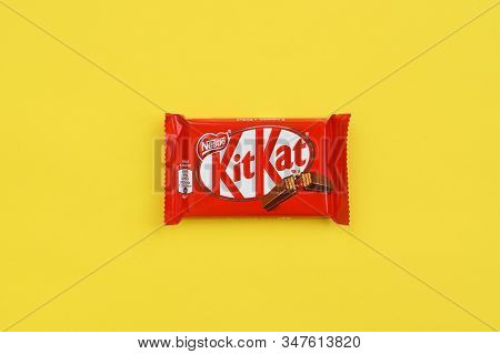 Kit Kat Chocolate Bar In Red Wrapping Lies On Yellow Background. Kit Kat Created By Rowntrees Of Yor