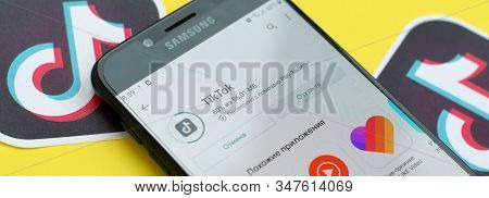 Tiktok Application In Playmarket On Samsung Smartphone Screen On Yellow Background. Tiktok Is A Popu