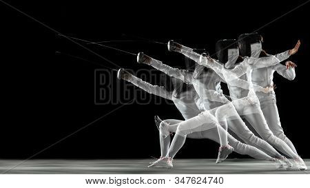 Teen Girl In Fencing Costume With Sword In Hand On Black Background In Strobe Light. Young Female Mo