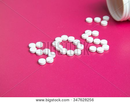 Sos Word Made Of Pills And Capsules On A Pink Background. Pills On A Blue Background. Word Sos.