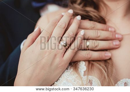 Married Couple. Bride And Groom Holding Each Other Hands With Wedding Rings Jewellery.