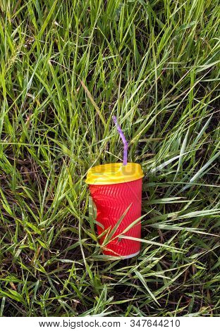 Bright Red Plastic Cup With Yellow Lid And Purple Bendy Drinking Straw (tube) In The Grass.