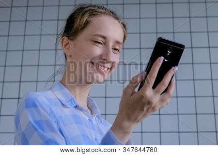 Communication, Lifestyle, Online Technology Concept. Positive Woman In Plaid Shirt Using Smartphone,
