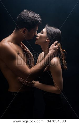 Side View Of Handsome Muscular Man Kissing Beautiful Girlfriend Isolated On Black
