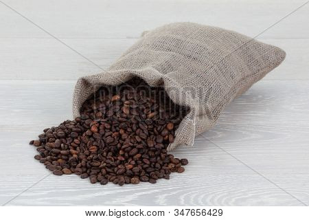Coffee Beans And Hessian Bag On Wood Surface