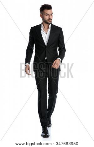 good looking formal business man wearing black tuxedo walking with loose hands and looking away pensive against white studio background