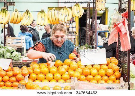 Subotica, Serbia - April 4, 2015: Senior Woman Selling Bananas And Oranges On Subotica Green Market