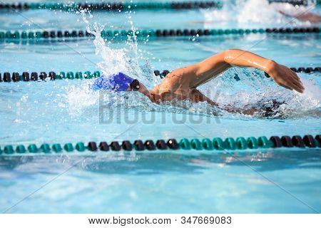Unrecognizable freestyle swimmer in a race, some motion blur, focus on arm and water splash