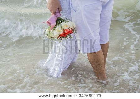 The View Of The Newlyweds Legs Standing On The Beach.