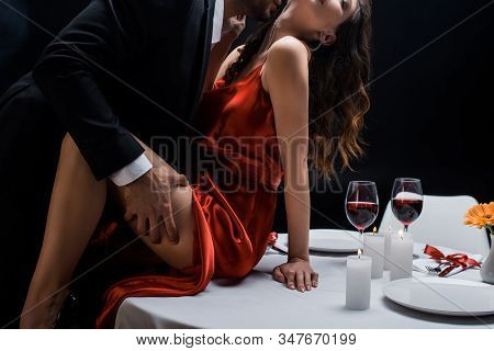 Cropped View Of Man In Suit Holding Hip Of Beautiful Woman On Served Table With Wine Isolated On Bla