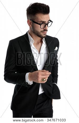 side view of a handsome formal businessman wearing black tuxedo,eyeglasses,ring preparing to grab something from pocket cautious against white studio background