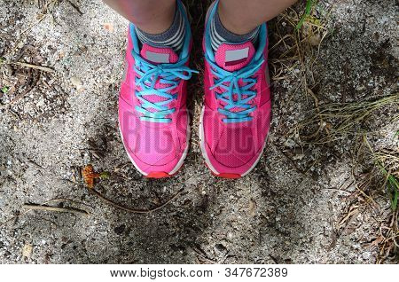 Woman Leg With Pink Sport Shoe On Sand Floor At The Beach