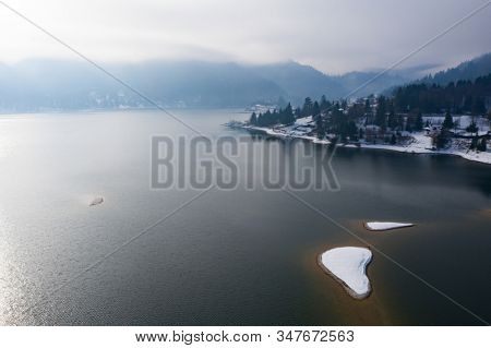 Winter magic landscape with scenic frozen mountain lake at Colibita, Romania.
