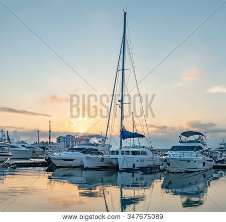 Yachts At The Pier. Beautiful Clear Sunset In The Sea Harbor With Moored Yachts.