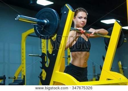 Fitness Girl Posing Near The Barbell In A Modern Gym. Muscles Woman Showing Sixpack Abs.