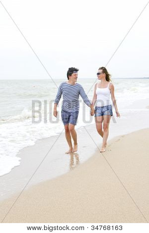 Happy Young Couple Enjoying Together At The Beach
