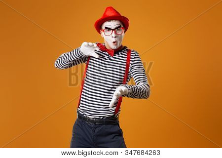 Mime man in white gloves and red hat looking at camera on orange background