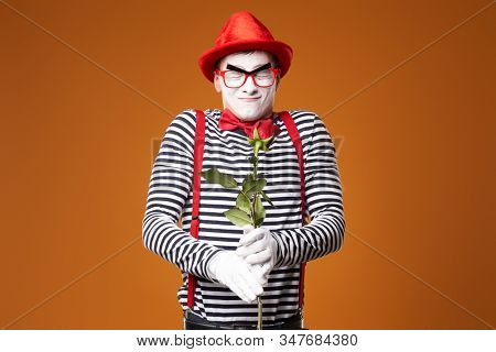 Mime in red hat, glasses and vest with rose in hands on orange background