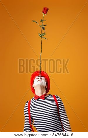 Mime man in vest and red hat looking up with rose on his forehead isolated