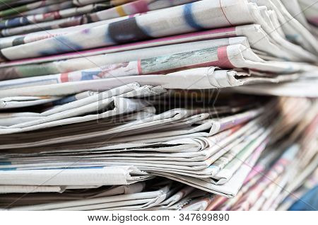 Newspapers Folded And Stacked On The Table. Closeup Newspaper And Selective Focus Image.