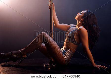 Side View Of Seductive Stripper In Lingerie Dancing Striptease Near Pole On Black