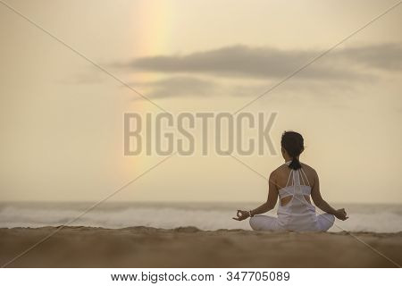 Yoga Lotus Pose Meditation Practice Of Young Asian Female On An Beach With Rainbow Background.