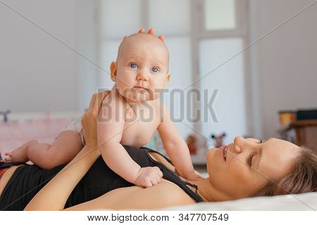 Mom Lying Down On Bed And Infant Baby Lies On Her Stomach