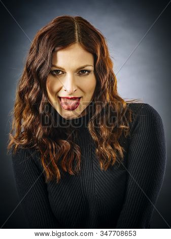Beautiful Redhead Woman Looking At Camera And Sticking Out Her Tongue.