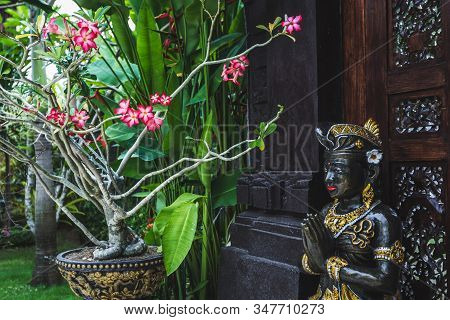Black And Gold Statuette Of A Hindu Deity In Ubud Garden In Bali. Symbolism And Religion In Indonesi