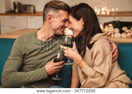Image of happy passionate couple drinking red wine from glasses while having romantic candlelight dinner at home