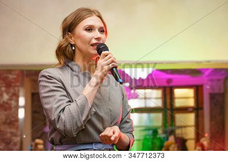 A Woman Speaks Into A Microphone, Gives A Lecture About Business. Conference Training Seminar Busine