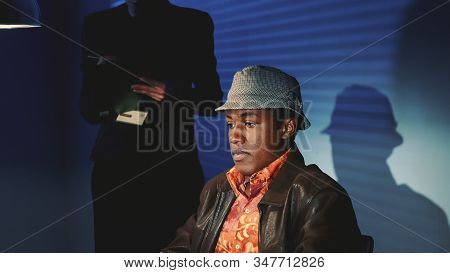 Close-up Of Accused Black Man In Hat Covering His Face With His Hands During Interrogation. In The B