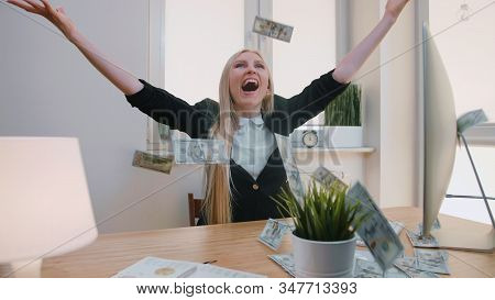 Elegant Blond Female Sitting At Desk At Workplace With Computer Holding In Hands Bundle Of Cash Look