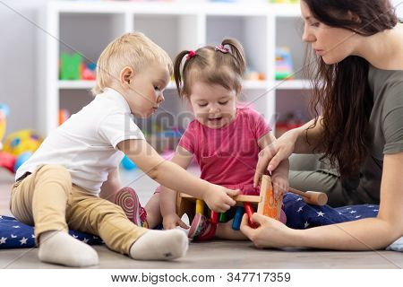 Preschooler Children Playing With Educational Wooden Toys At Kindergarten Or Daycare Center. Toddler