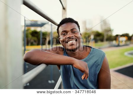 Smiling Portrait Of A Sporty Young African American Man Leaning On Bar At The Public Park Looking To