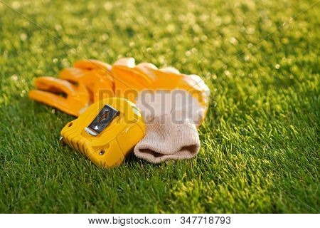Artificial Grass Background With Protective Glooves And Measuring Tape