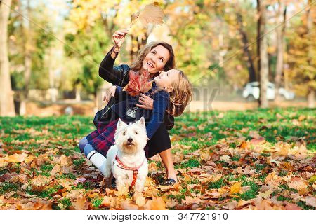 Happy Family With Dog Having Fun In Autumn Park. Mother And Her Daughter Playing With Dog Outdoors.
