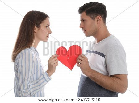 Couple Tearing Paper Heart On White Background. Relationship Problems
