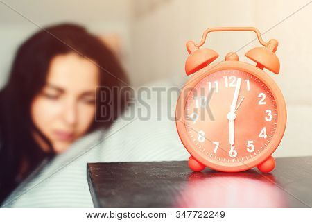 Alarm Clock At Foreground In Bedroom At Home. Young Sleeping Woman In Bed. Early Morning Awakening.