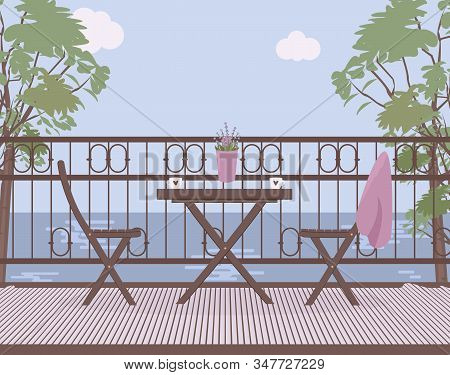 Wooden Garden Furniture On The Balcony With Wrought Iron Railings With A Lilac Pot With Lavender Flo