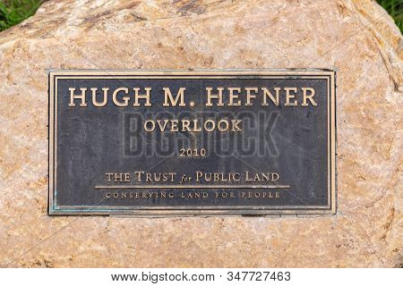 Los Angeles, California, USA - January 26, 2020:   Photograph of the Hugh M. Hefner overlook trail sign near scenic view point overlooking the famous Hollywood sign in Griffith Park.