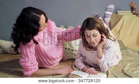 Mom Listening Her Daughter Reading Bedtime Storybook, Stroking Loving Daughter