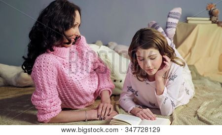 Mom Attentively Listening Her Daughter Reading Bedtime Storybook, Happy Family
