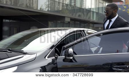 Handsome Afro-american Man Sitting In His Brand-new Car, Leaving Showroom