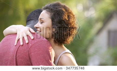 Positive And Cheerful Spouses Embrace Each Other In Warm And Tender Cuddles