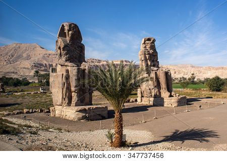Memnon Colossi - The Ancient Guards Of The Temple Of Amenhotep Iii. Luxor, Egypt.
