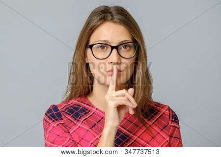 Portrait Of Emotional Woman Holding Index Finger At Her Lips, Saying Shh